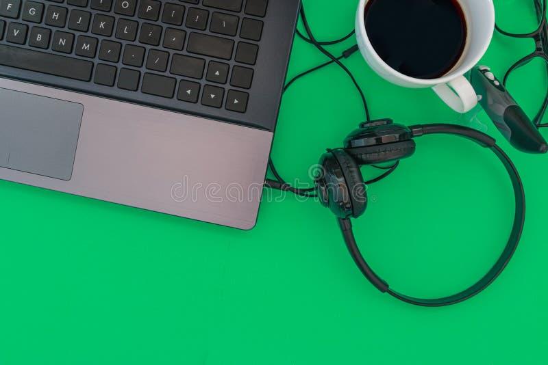 Koffiekop en hoofdtelefoons van laptop computer op een groene heldere toonachtergrond Hoogste mening royalty-vrije stock afbeelding