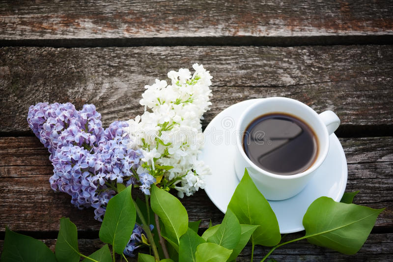 Koffiekop en kleurrijke lilac bloemen op houten achtergrond royalty-vrije stock afbeelding