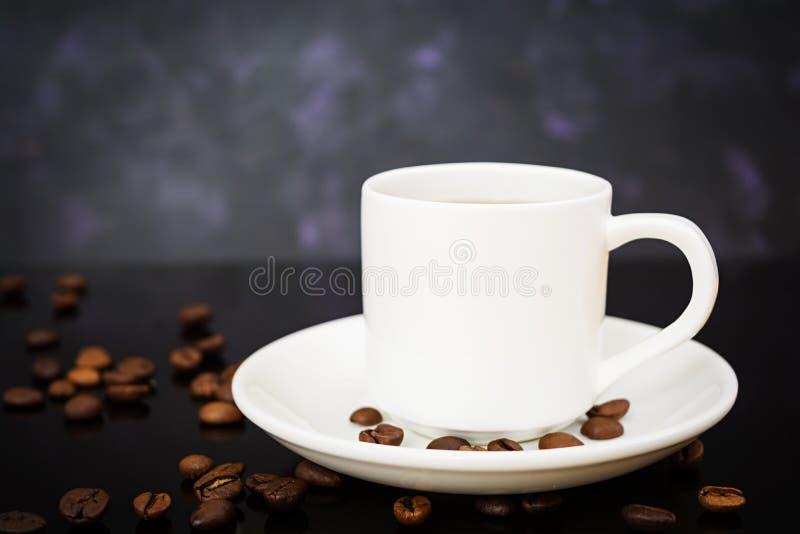 Koffiekop en koffiebonen op donkere achtergrond royalty-vrije stock afbeelding