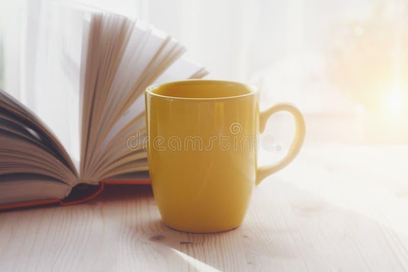 Koffiekop en open boek op houten lijst stock foto