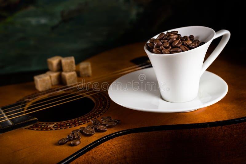 koffiekop en rietsuiker op een gitaar stock foto