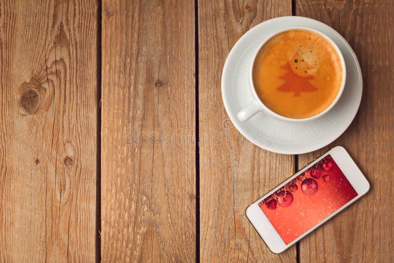 Koffiekop en smartphone met Kerstmisbeeld De viering van de Kerstmisvakantie stock fotografie