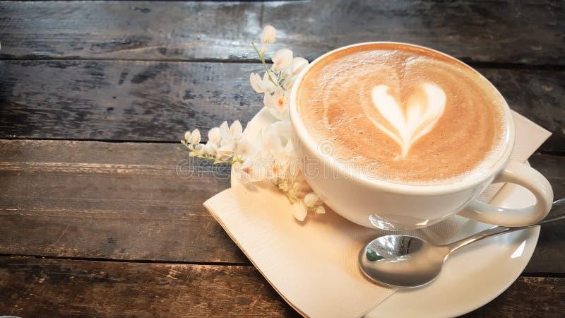 Koffiekop en uiterst kleine witte bloem op houten lijst royalty-vrije stock foto