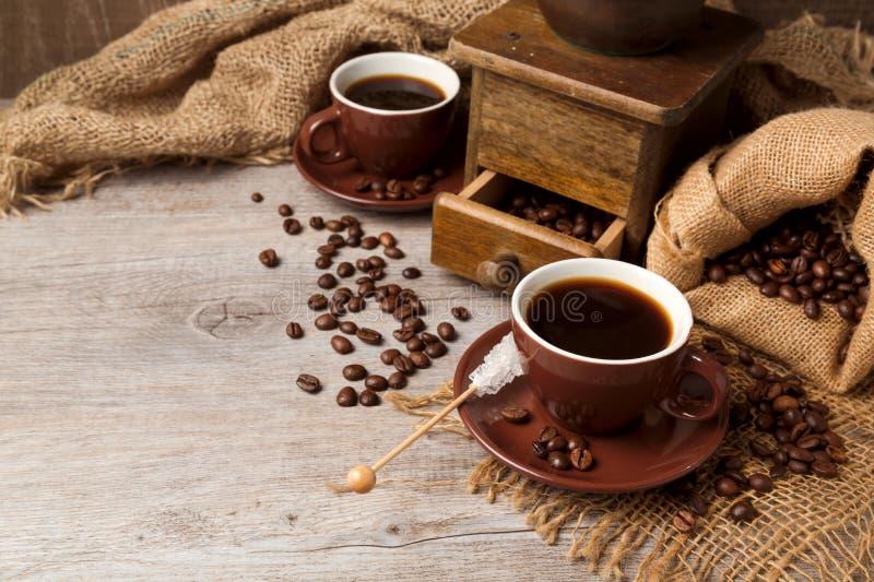 Koffiekop en uitstekende koffiemolen over houten achtergrond met jute stock afbeelding