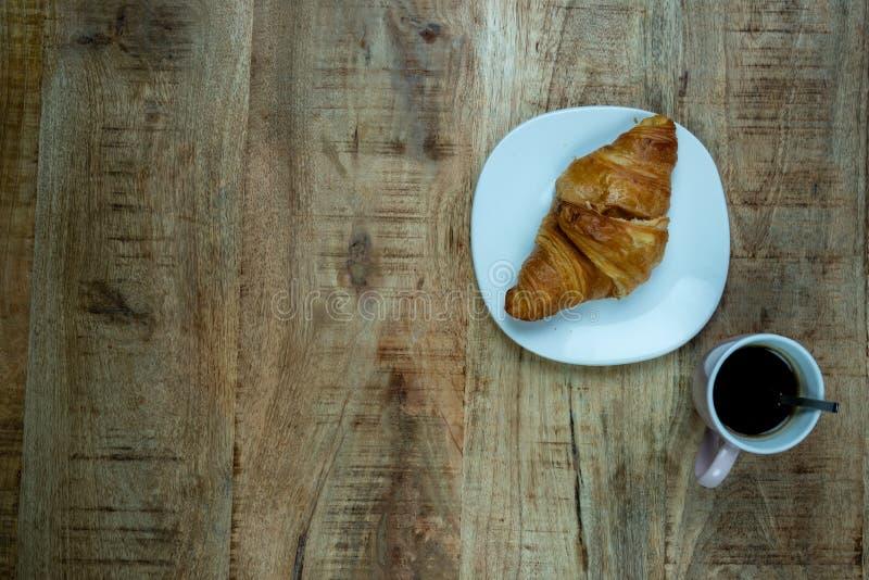 Koffiekop en verse gebakken croissants op houten achtergrond Hoogste mening Voorbeeld van een ontbijt stock fotografie