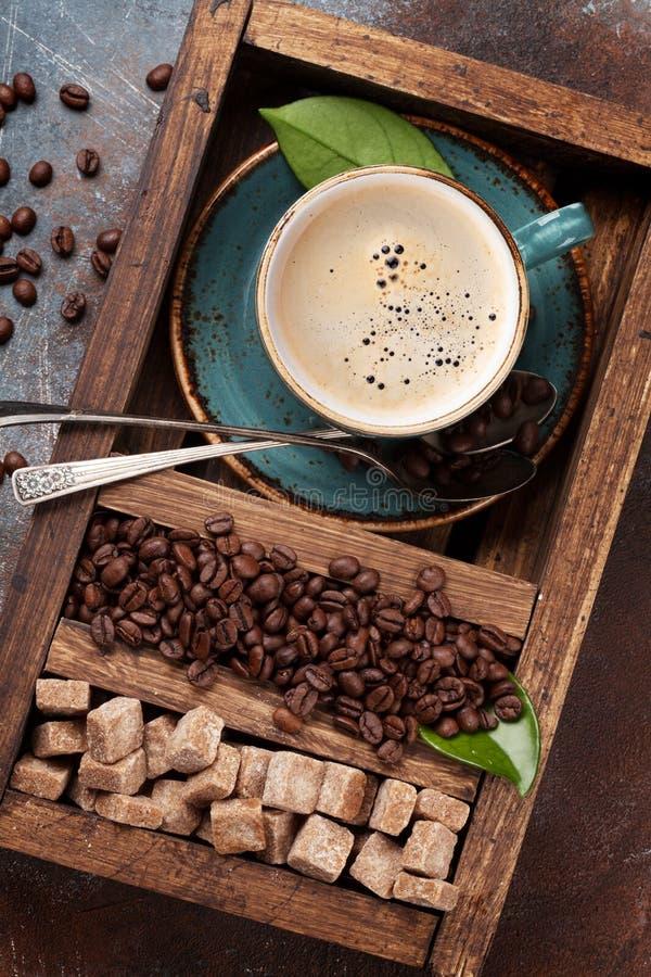 Koffiekop, geroosterde bonen en bruine suiker stock foto's