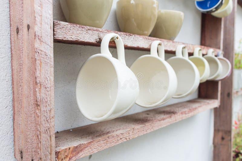 Koffiekop het hangen op houten plank royalty-vrije stock afbeeldingen