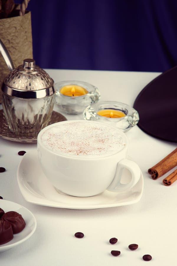 Koffiekop, koffiebonen, chocoladesuikergoed en kaarsen op een witte lijst stock afbeelding