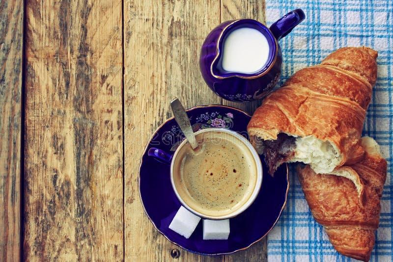 Koffiekop, melkkruik en croissant met chocolade royalty-vrije stock foto's
