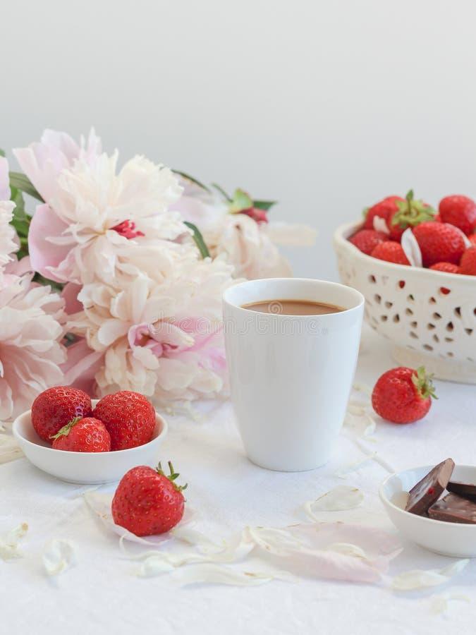 Koffiekop met chocolade, aardbeien en pioenen op de achtergrond royalty-vrije stock fotografie