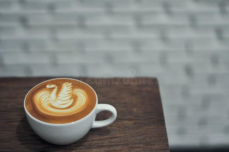 Koffiekop met de zwaanpatroon van de lattekunst op de houten lijst stock afbeeldingen