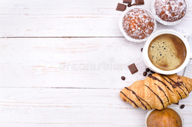 Koffiekop met een croissant en een cake stock foto