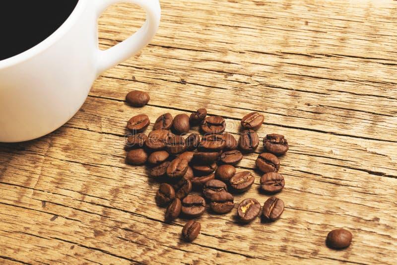 Koffiekop met geroosterde koffiebonen naast het - sluit omhoog studioschot Gefiltreerd beeld: kruis verwerkt uitstekend effect royalty-vrije stock fotografie