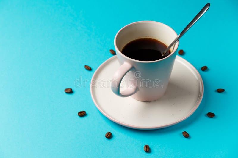 Koffiekop met lepel op schotel en koffiebonen tegen blauwe achtergrond die wijzerplaat vormen Koffie als symbool van ochtendenerg stock afbeeldingen
