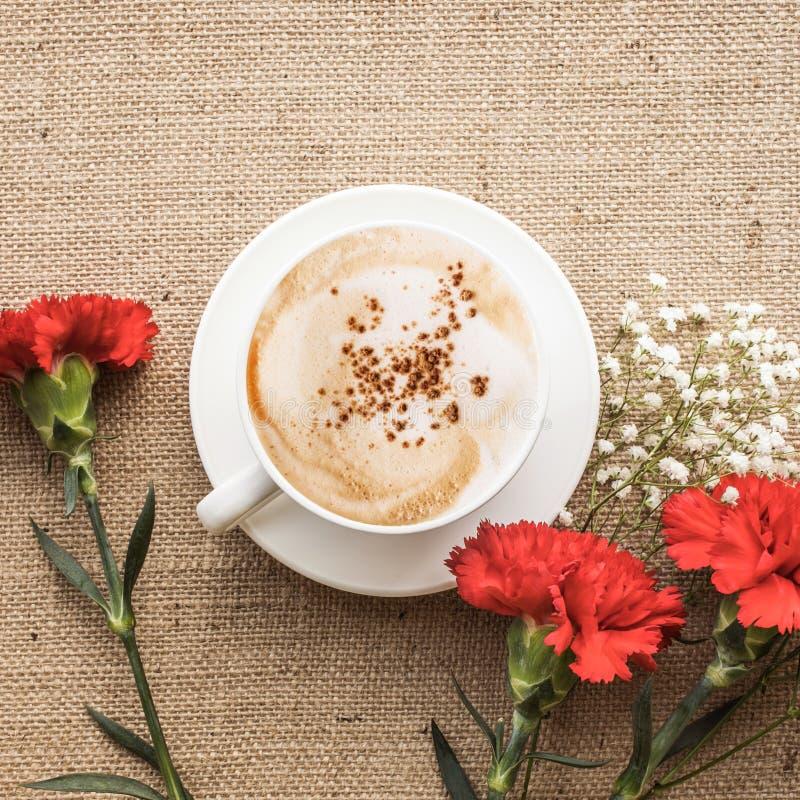 Koffiekop met rode bloem op juteachtergrond Vlak leg stock afbeeldingen