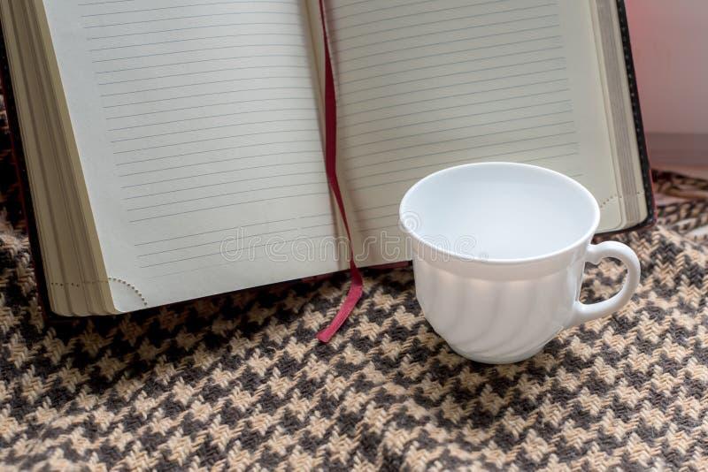 Koffiekop met schuim op de achtergrond van het boek met schone pagina's royalty-vrije stock afbeelding