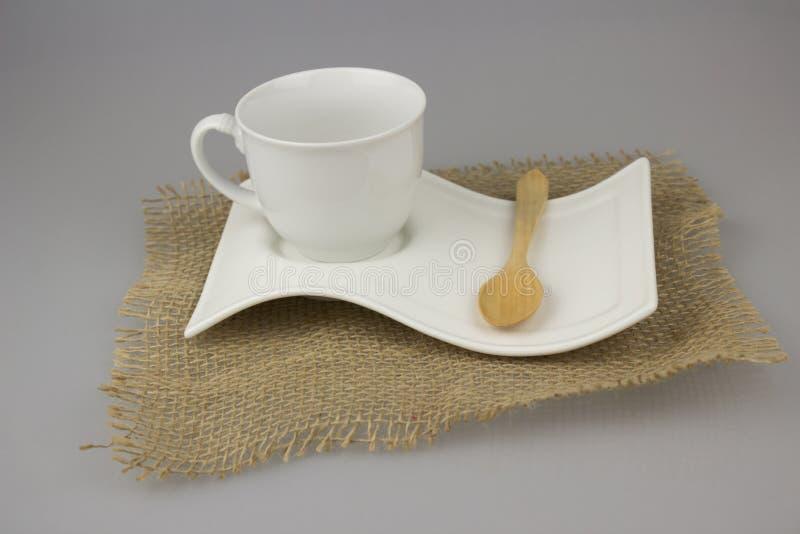 Koffiekop met theelepeltje op jute texite royalty-vrije stock afbeeldingen