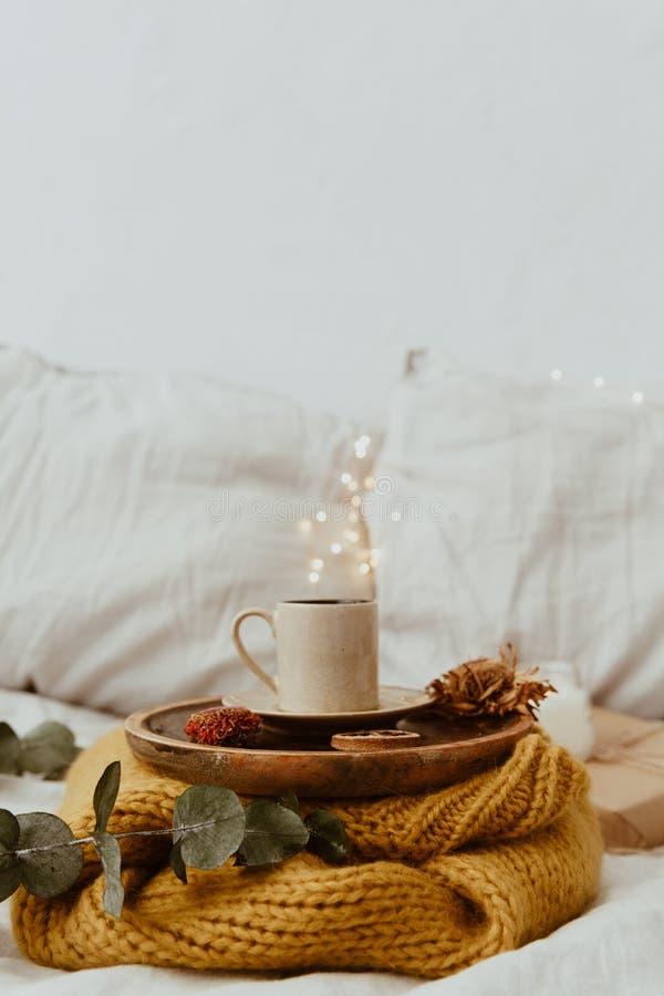 Koffiekop op een houten dienblad en een warme sweater met achtergrond bokeh onduidelijk beeld van lichten wordt geplaatst dat Och stock foto's