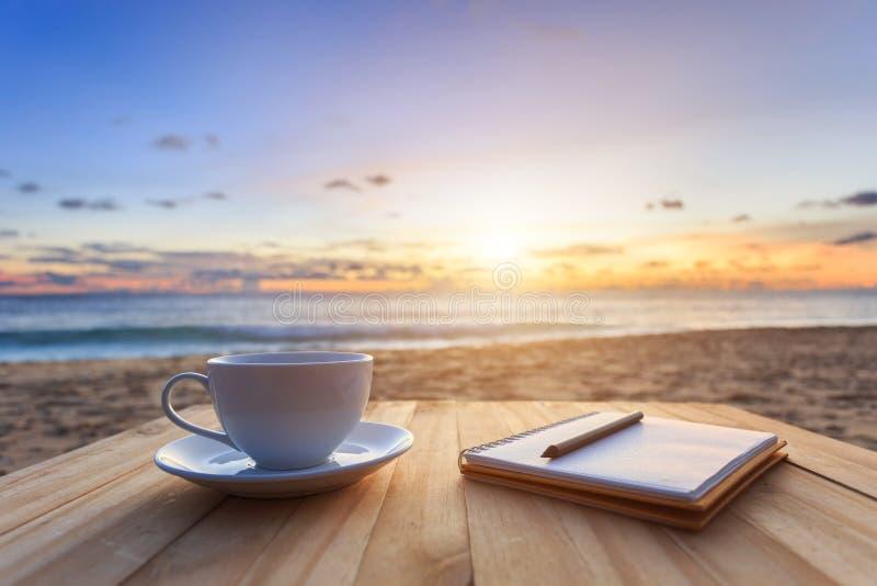 koffiekop op houten lijst bij zonsondergang of zonsopgangstrand royalty-vrije stock foto