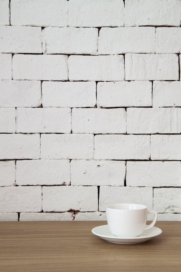 Koffiekop op houten lijst met witte baksteenachtergrond stock afbeeldingen