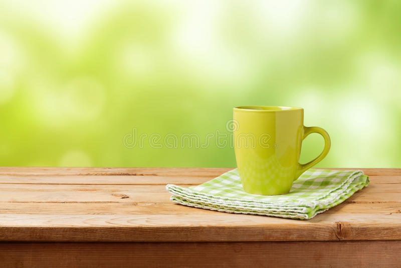 Koffiekop op houten lijst over groene bokehachtergrond Spot omhoog voor de vertoning van het embleemontwerp royalty-vrije stock fotografie