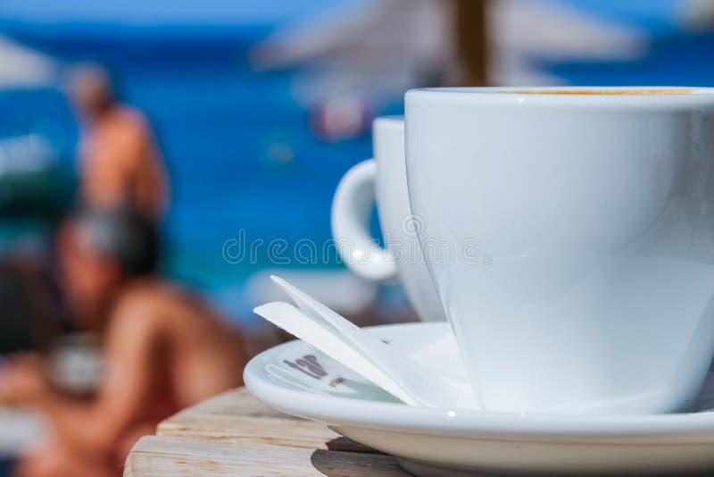 Koffiekop op rondetafel in koffieterras op de oude pijler Strandkoffie met de mening over het overzees in zonnige dag en met royalty-vrije stock fotografie