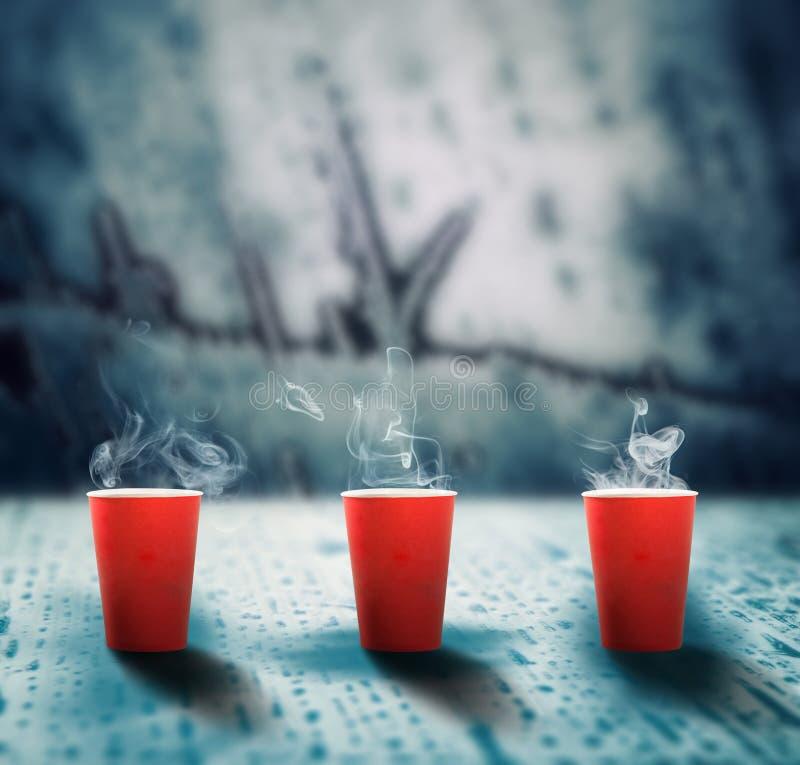 Koffiekopjes op smeltend ijs stock afbeeldingen