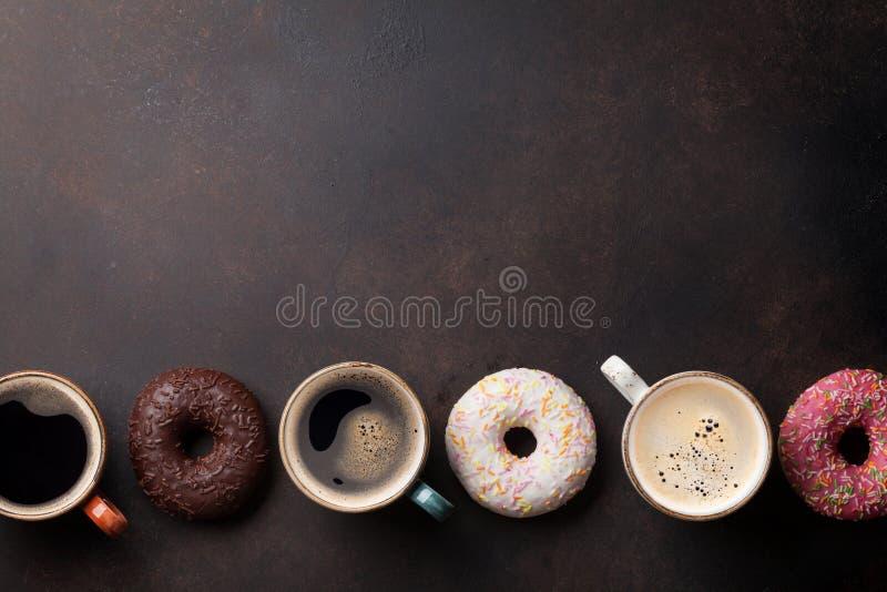 Koffiekoppen en kleurrijke donuts stock afbeeldingen