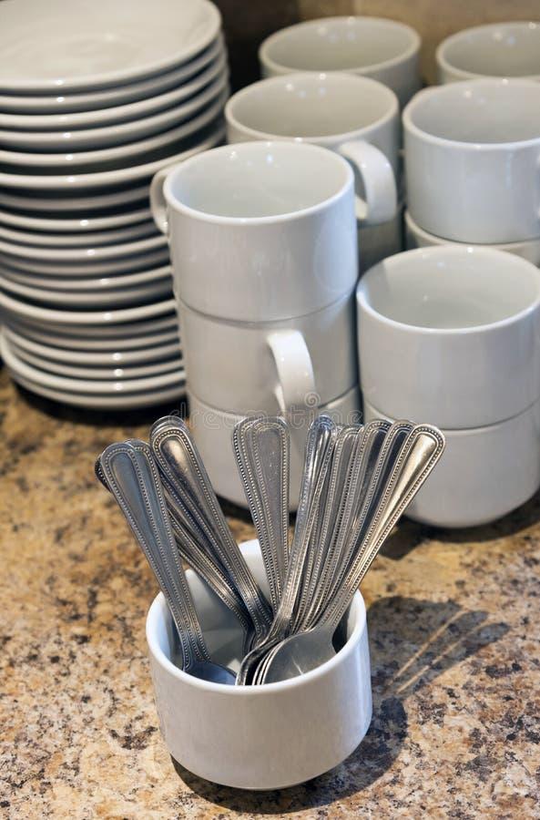 Koffiekoppen en lepels die op gebruik wachten stock fotografie