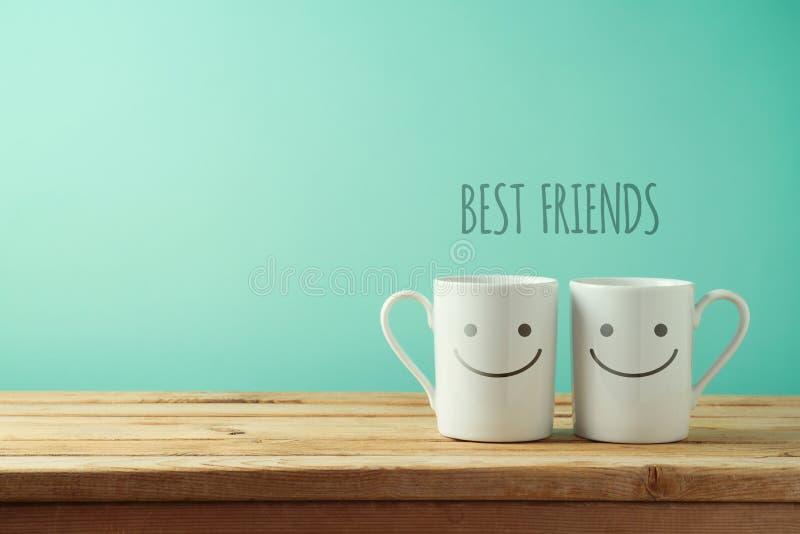 Koffiekoppen met grappige gezichten op houten lijst stock afbeeldingen