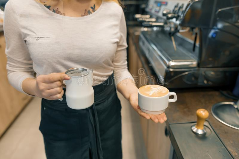 Koffiekunst, close-up van de jonge vrouwelijke melk van de baristaholding voor pre stock foto