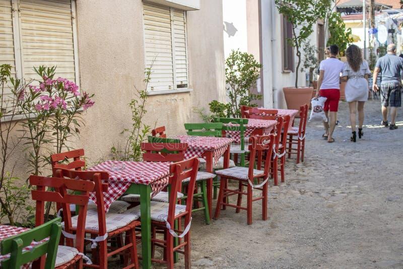 Koffielijsten en stoelen in de straat Mensen die op de straat lopen stock afbeeldingen