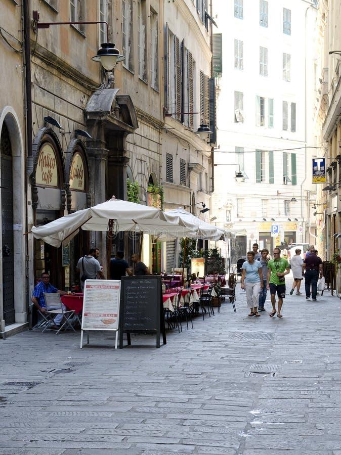 Koffielijsten en toeristen van keistraat in Genua, Italië stock afbeeldingen