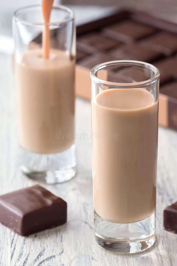 Koffielikeur in een glas met chocoladesnoepjes stock foto