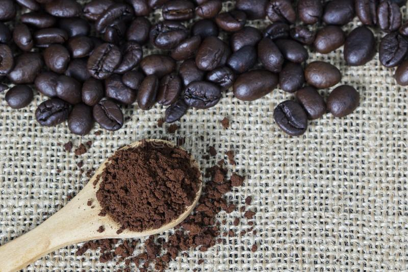 Koffiemalen in houten lepel op jute met de achtergrond van koffiebonen De ruimte van het exemplaar stock afbeeldingen