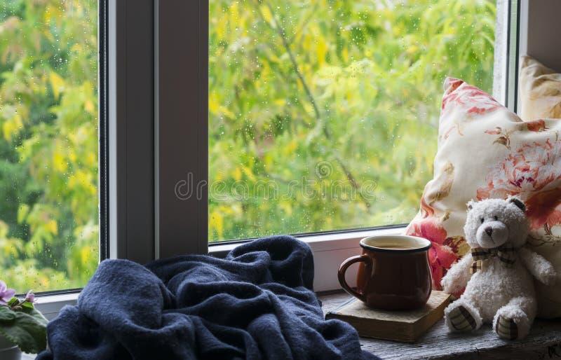 Koffiemok, boek, Teddybeer, hoofdkussens en een plaid op de lichte houten oppervlakte tegen venster met regenachtige dagmening Ui royalty-vrije stock fotografie