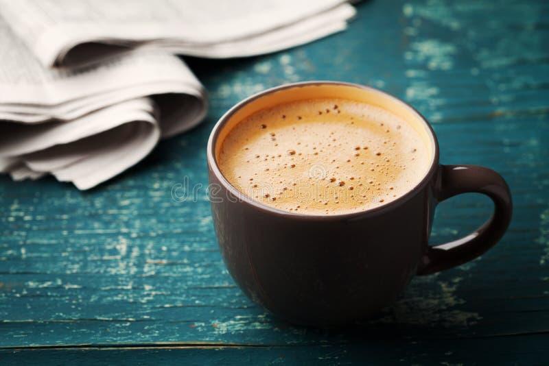 Koffiemok met krant op wintertalings rustieke lijst, comfortabel ontbijt stock fotografie