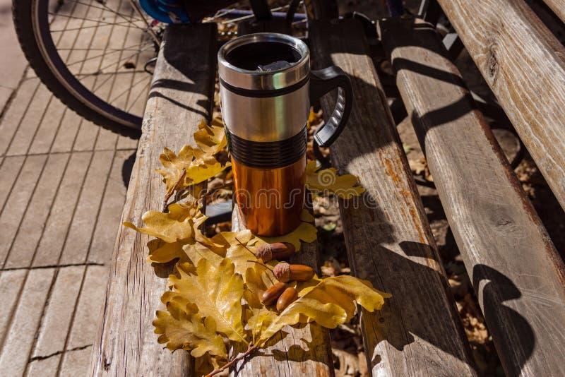 Koffiemok op de houten bank in het park stock foto