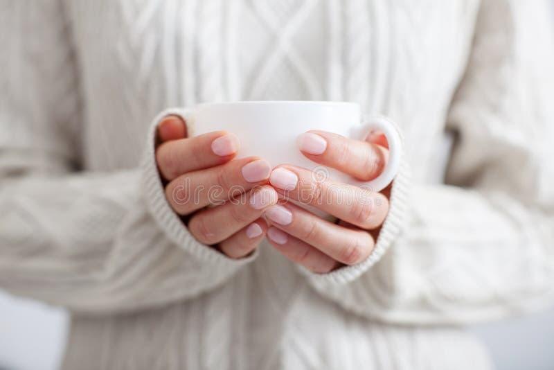 Koffiemok in vrouwelijke handen stock foto