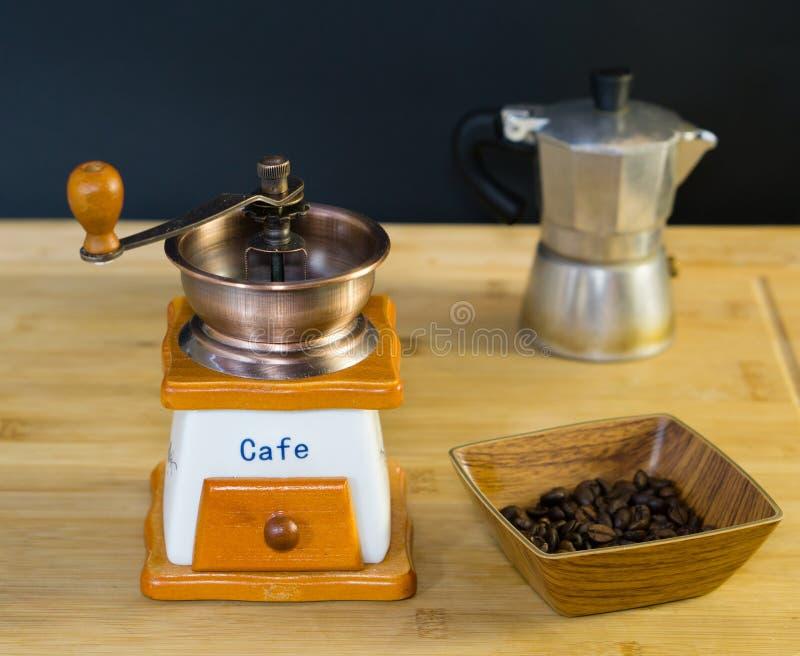Koffiemolen en geroosterde koffiebonen van de kant in een houten schotel royalty-vrije stock foto