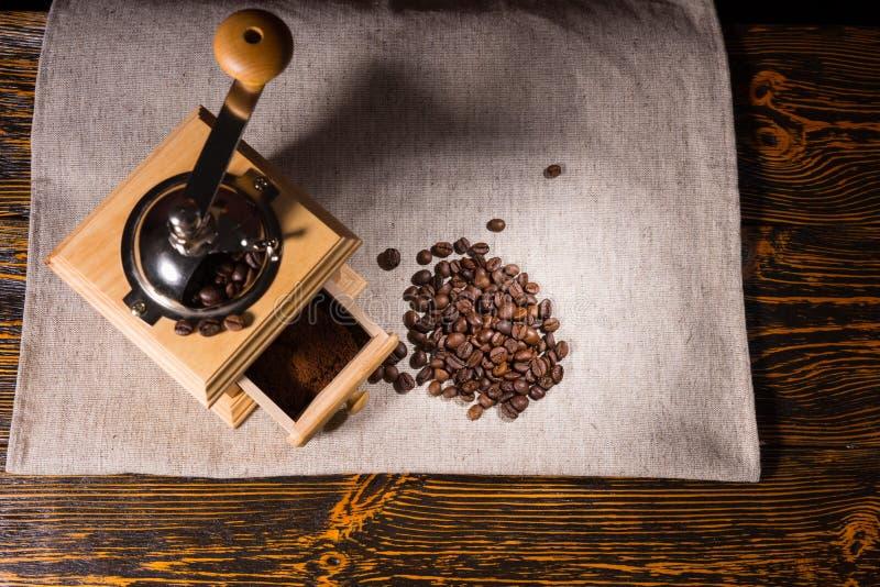 Koffiemolen, grond en bonen op tafelkleed royalty-vrije stock afbeelding