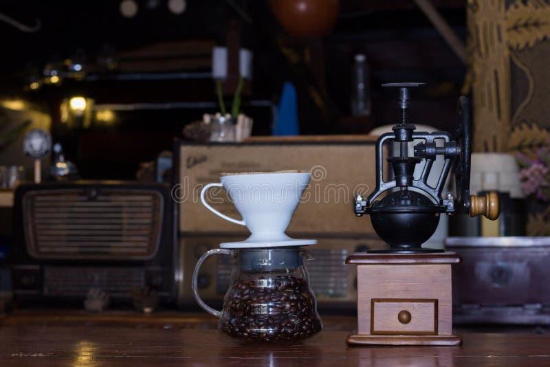 Koffiemolen met koffiebonen in glas op de lijst stock foto