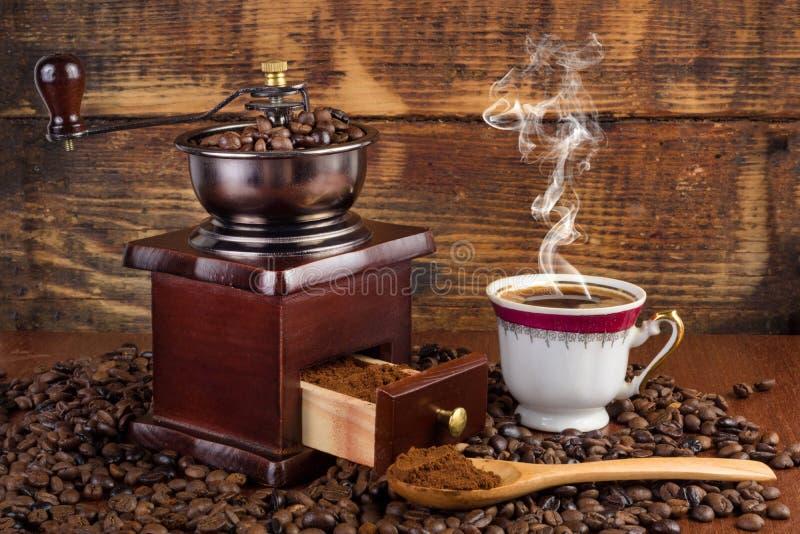 Koffiemolenmolen en kop van koffie met rook en houten lepel op retro achtergrond royalty-vrije stock foto's