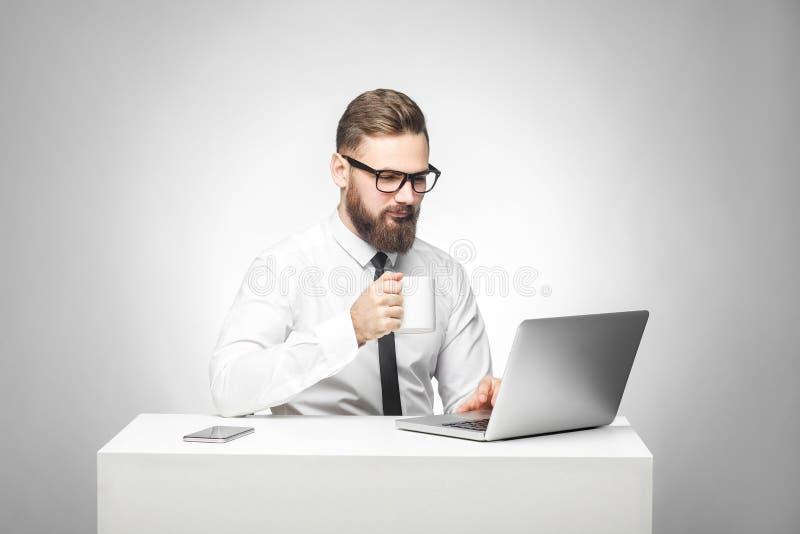 Koffiepauze! Het portret van knappe gelukkige gebaarde jonge zakenman in wit overhemd en de avondkleding zitten in bureau en hebb stock foto