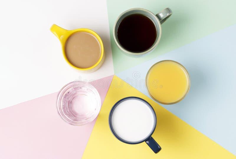 Koffiethee en andere dranken in kleurrijke koppen op een witte achtergrond, hoogste mening stock afbeelding