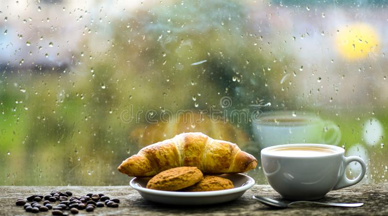 Koffietijd op regenachtige dag Verse gebrouwen koffie in witte kop of mok op vensterbank Natte glasvenster en kop van heet stock foto