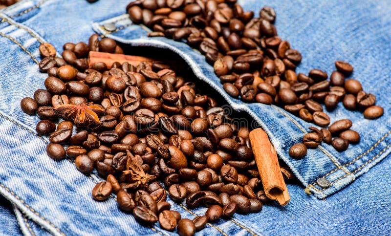 Koffiewinkel of opslag Textuur en achtergrondconcept Verse geroosterde koffie dicht omhoog Bonen en kruiden in jeanszak royalty-vrije stock afbeelding