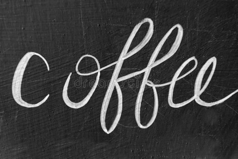 Koffiewoord met de hand geschreven met krijt op bord stock foto