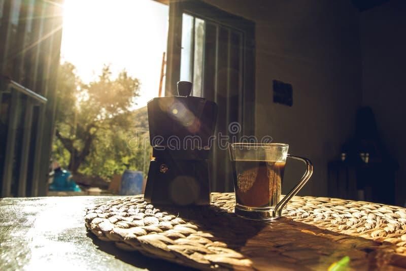 Koffiezetapparaat en een kop van koffie op een lijst stock foto's