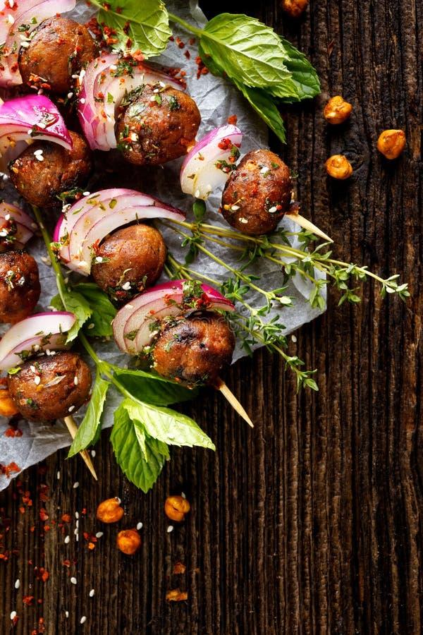 Koftavleespennen, vleesballetjes en rode ui met toevoeging van verse munt en thyme, heerlijke oosterse keuken stock afbeeldingen